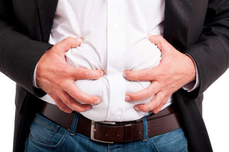 Man having indigestion after a business lunch as abdominal pain concept Standard-Bild