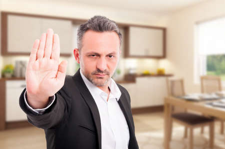 Serious realtor showing stop gesture with palm as warning concept Standard-Bild