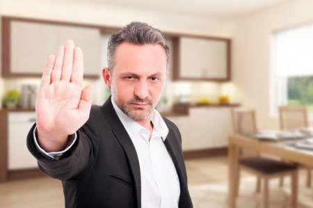 Ernstige makelaar in onroerend goed die eindegebaar met palm tonen als waarschuwingsconcept