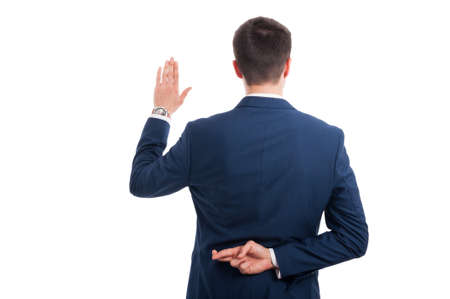 Salesman promising an oath with crossed fingers behind his back as false statement concept isolated on white background Stock Photo