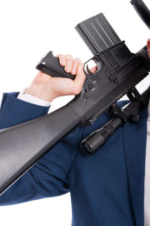 Closeup of male secret agent holding a rifle on his shoulder in closeup