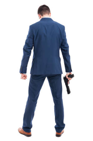 Powerful killer with a gun standing with back at the camera on white background Stock Photo