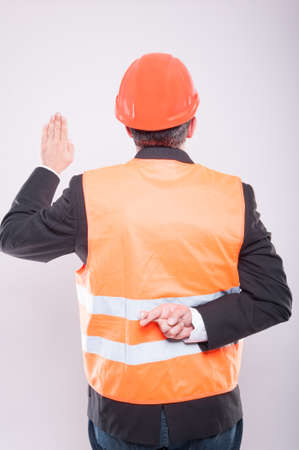 Back view of engineer wearing hardhat and reflective vest making fake oath gesture on grey background