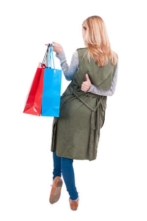 Back view of fashion girl at shopping with gift bags doing like sign on white background