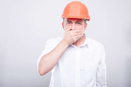 Portrait of contractor wearing hardhat covering his mouth with hand like mute concept on grey background