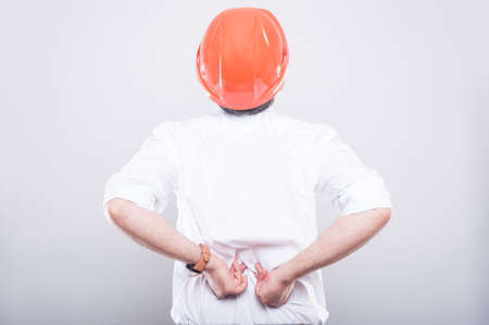Back view of architect wearing hardhat suffering back pain on grey background