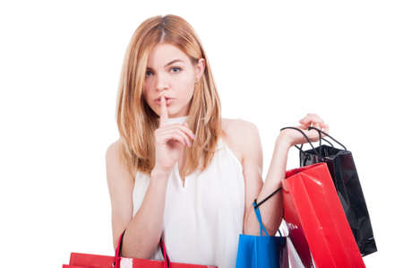 Young sexy shopping female show you to keep silence while buying expensive gifts isolated on white background Stock Photo