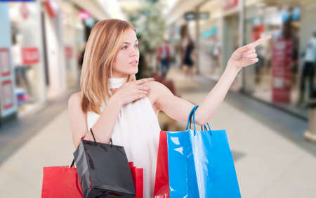 Stylish woman with shopping bags pointing at something inside the mall