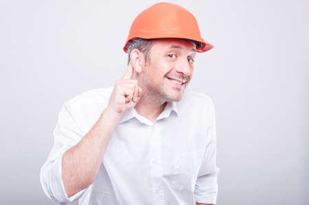 El retrato del contratista que desgasta la fabricación del casco de protección no puede oír gesto en fondo gris
