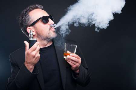 Rich man exhaling vapor from an electronic cigarette and enjoying a glass of scotch on dark background Stock Photo