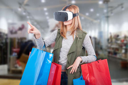 Woman customer experience virtual shopping thru modern headset and pointing finger at something 스톡 콘텐츠