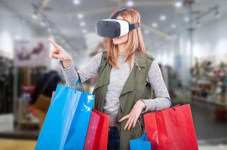 Klientka kobieta doświadcza wirtualnych zakupów przez nowoczesny zestaw słuchawkowy i wskazując palcem na coś Zdjęcie Seryjne