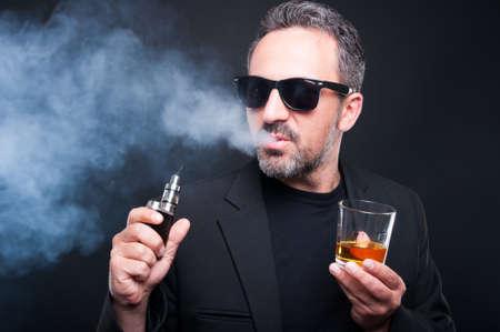 joven fumando: Hombre fumando un cigarrillo electrónico y beber alcohol fino sobre fondo negro