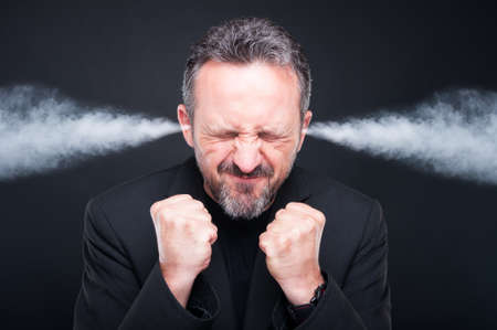 Angry frustrated man with exploding head and steam coming out of his ears on dark background Stock Photo