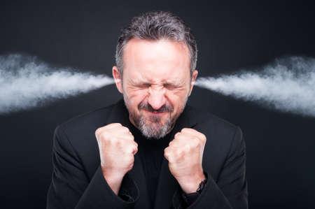 Verärgerter frustrierter Mann mit dem speziellen Kopf und Dampf , die von den Ohren auf dunklem Hintergrund herauskommt