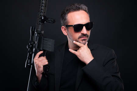 menace: Pensive gangster in black suit with dangerous rifle on dark background