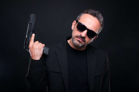 Killer man with pistol on dark background looking at the camera as gang and mafia concept
