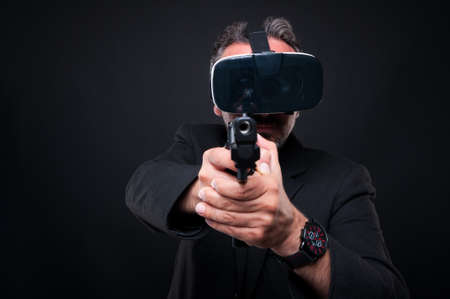 simulator: Mafia member aiming gun at the camera while wearing modern glasses as vr gaming concept Stock Photo