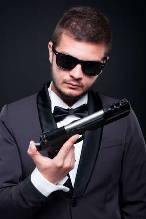 deadly: Powerful gangster with a gun or pistol isolated on black background