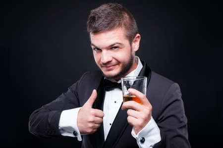 Portrait of elegant young man in suit toasting with glass of alcohol isolated on black background Stok Fotoğraf