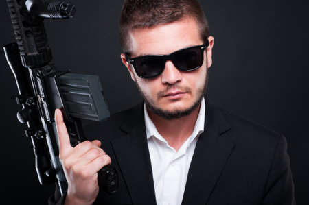 menace: Portrati of attractive man with a shotgun standing on black background