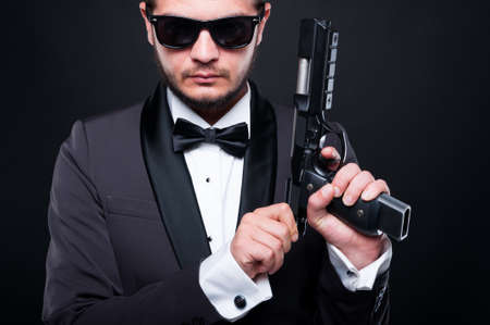 menace: Portrait of shooter loading pistol in closeup view being ready to attack on dark background