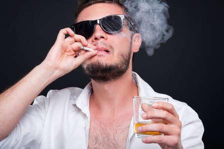 Close-up portret van mafia moordenaar rokende sigaar en drinken alcohol op zwarte achtergrond Stockfoto