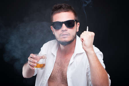 menace: Aggressive young male fighting while drinking whiskey and smoking on dark background