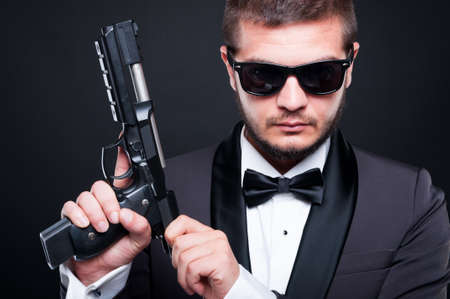 Portrait of serious gunman loading the chamber of his gun in close-up view
