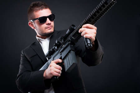 menace: Mafia man aiming up the machine gun with a serious expression on his face on dark background
