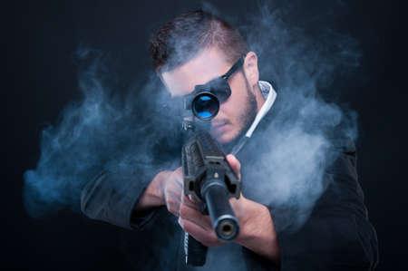 Mafia criminal aiming weapon at you thru smoke on black background