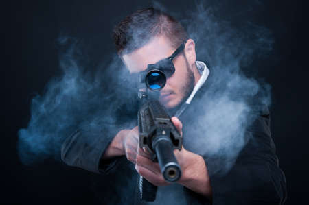 Mafia criminal aiming weapon at you thru smoke on black background