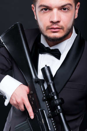 menace: Portrait of young gangster holding armed rifle on dark background as danger and violence concept Stock Photo