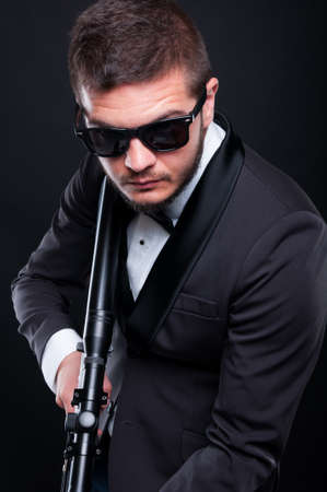 menace: Mafia guy with armed rifle preparing to shoot isolated on black background