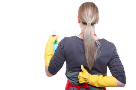 Housewife cleaning and showing thumb up behind her back on white background with advertising area