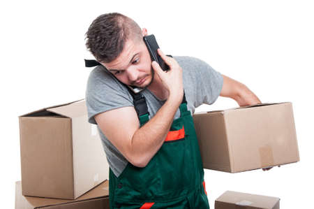 Mover guy holding cardboard box talking at phone looking very busy isolated on white background Stock Photo