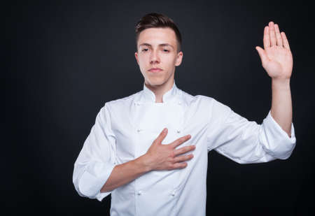 Honest cook rising his left hand and swearing to always tell the truth Stock Photo - 81139640