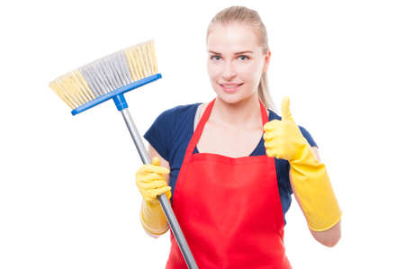Attractive young woman holding broom and smiling at camera while holding thumb up