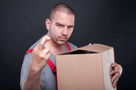 Mover man holding box wising bad luck with fingers crossed on black background