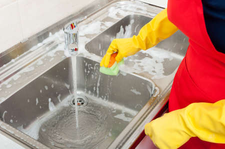 Person hands in yellow gloves cleaning the kitchen sink with disinfectant Stock Photo