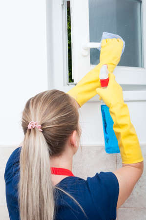 Back view of housekeeper cleaning window with rag and detergent spray