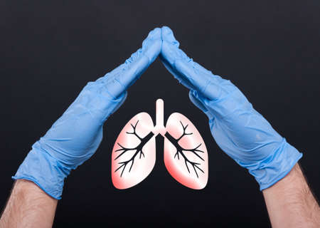 Medical assistant holding lungs between hands protecting from pulmonary disease isolated on black background Stockfoto