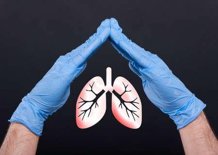 Medische assistent die longen tussen handen beschermen tegen longziekte geïsoleerd op zwarte achtergrond