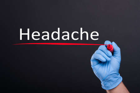 headaches: Hand writing inscription headache with marker in close-up on dark background