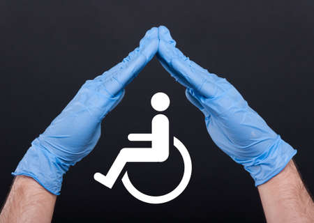 Conceptual image of help and care for handicapped person isolated on dark background