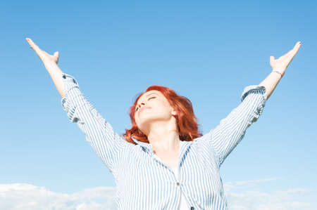 resting: Free happy woman enjoying nature with arms outstretched in the air Stock Photo