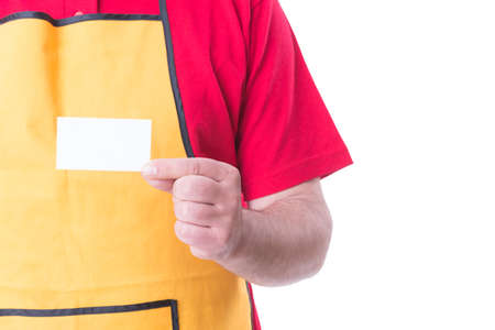 Salesman with apron showing empty visit card isolated on white background with text space