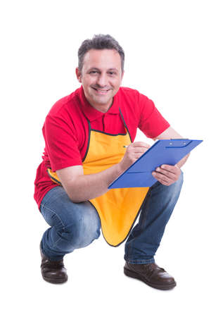 Smiling salesman counting products on supermarket shelf and taking notes on clipboard