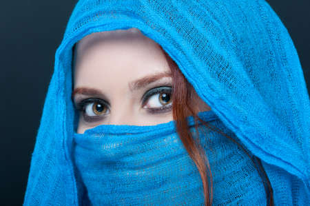 Closeup of gorgeous young woman wearing blue veil in photo studio