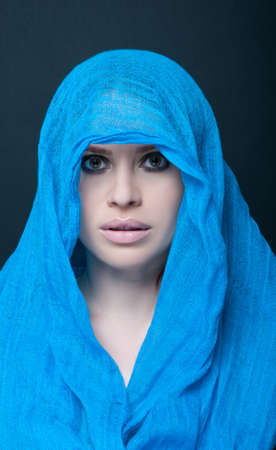 Attractive woman portrait with scarf over head posing sensual on dark background Stock Photo